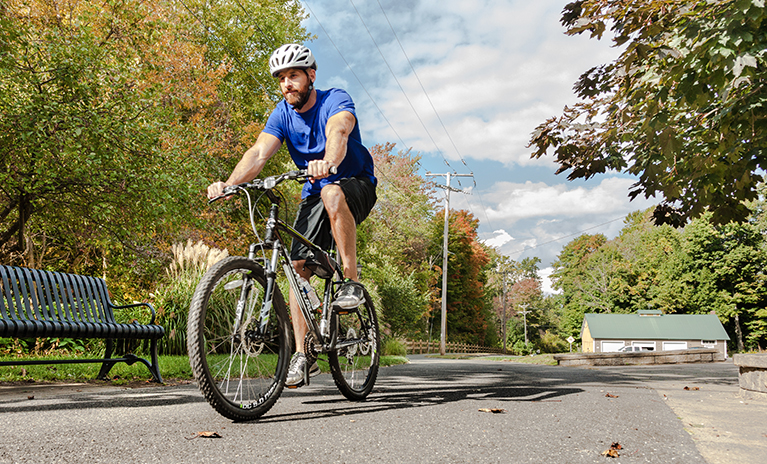 Man rides his bike through Middlebury on a sunny day