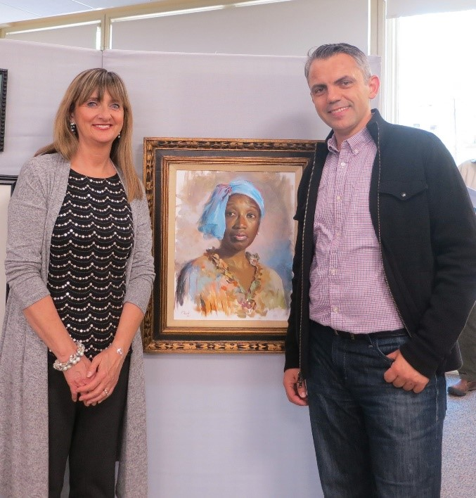 "Flladi Kulla poses with Ilona Blouin next to his award winning oil painting titled ""Alecia."""