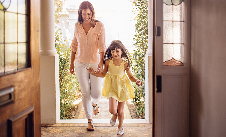 Young girl excitedly leads her mother through the entryway of their new home