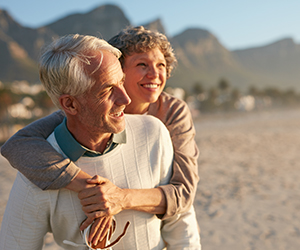Two elderly people embrace at sunset.