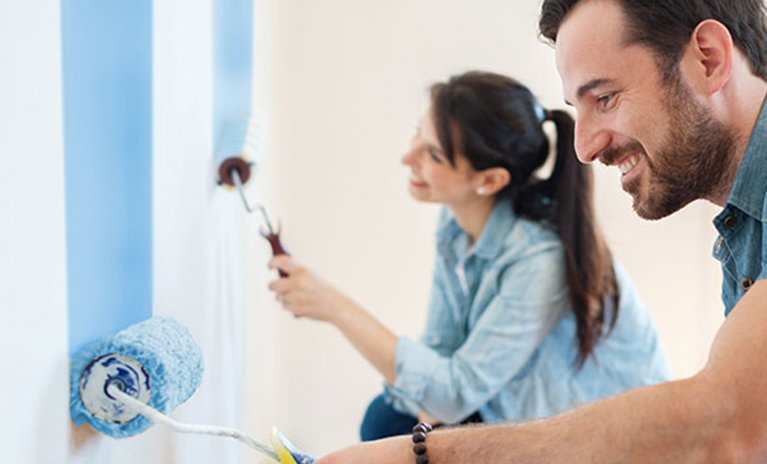 Man and woman painting walls with rollers