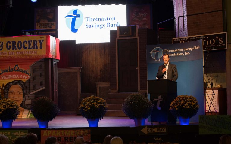 CEO Stephen L. Lewis speaks on stage at the Thomaston Savings Bank 2019 Foundation Night in front of a projected TSB logo.