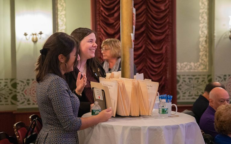 Two women smiling and laughing at a table at the 2018 Thomaston Savings Bank Foundation Night