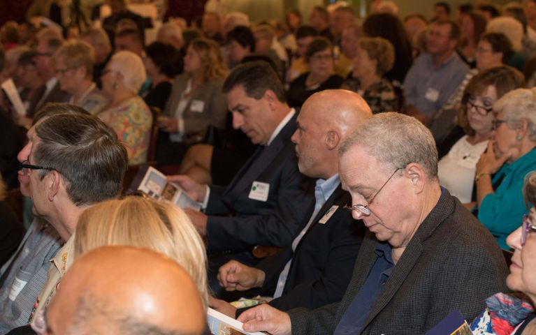 Seated attendees read through pamphlets in a crowded theater during the 2019 TSB Foundation Night.