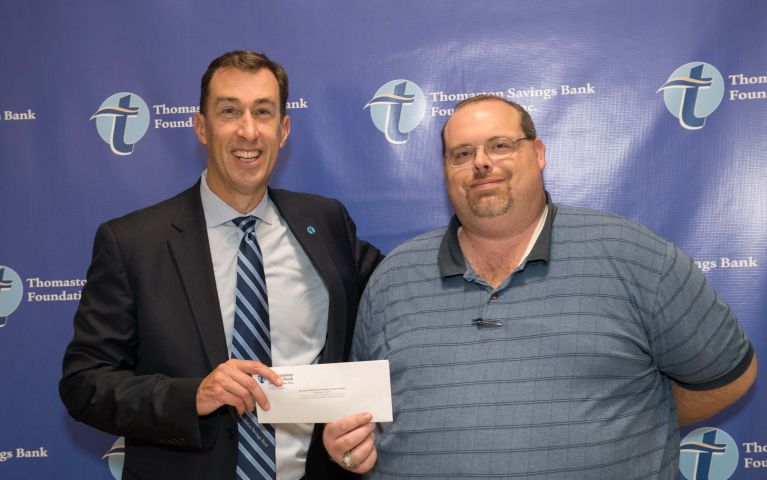 Stephen L. Lewis, CEO and President of Thomaston Savings Bank smiles next to a loyal TSB customer while presenting him a check at the 2019 Foundation Night.