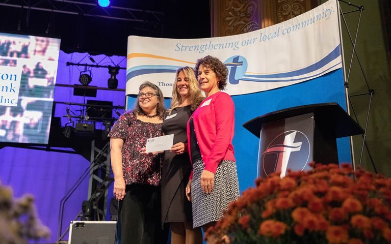 Three woman smiling with a check for a picture onstage at the 2018 TSB Foundation Night