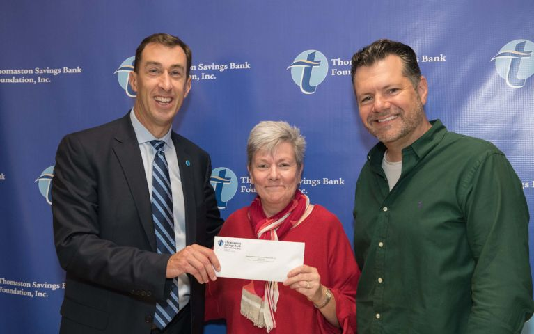 Two attendees pose with CEO of Thomaston Savings Bank while being presented with a check at the 2019 Foundation Night.
