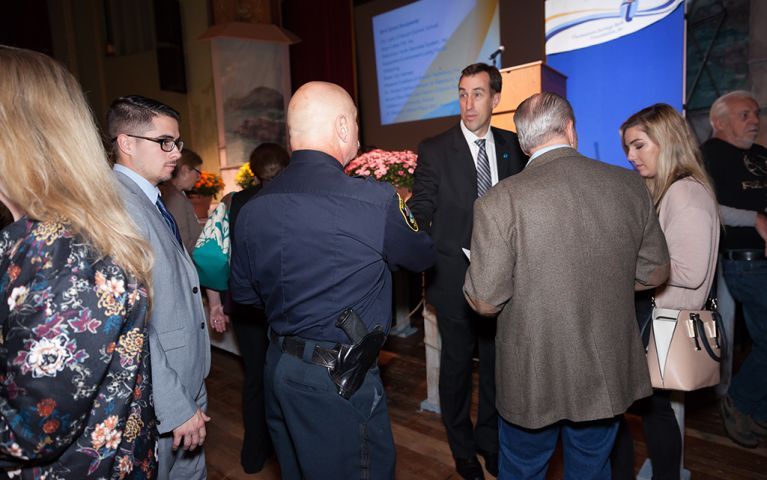 President of Thomaston Savings Bank, Stephen L. Lewis, talking with a police officer in a group at the 2017 TSB Foundation Night