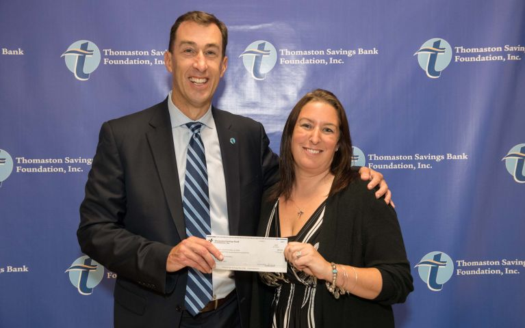 Thomaston Savings Bank's CEO Stephen L. Lewis presents a check to a local community member as they pose for a picture during the 2019 TSB Foundation Night.
