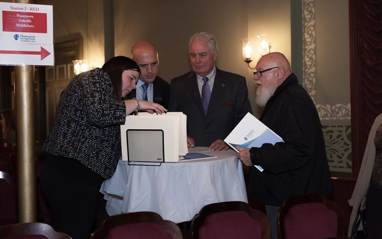 A woman and three men sifting through filing folders at a table at the 2017 TSB Foundation Night