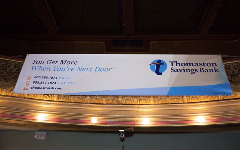 Banner with the words: You Get More When You're Next Door hanging from the balcony at the 2017 TSB Foundation Night