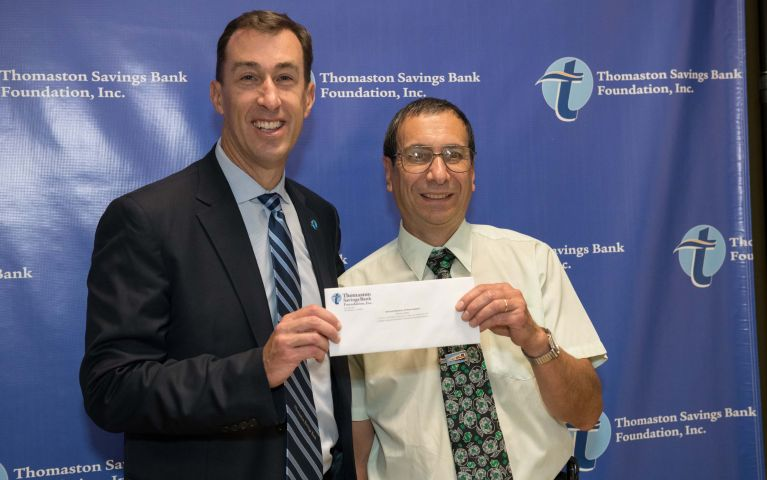 Stephen L. Lewis, President and CEO of Thomaston Savings Bank poses to present an envelope to member at 2019 TSB Foundation Night.