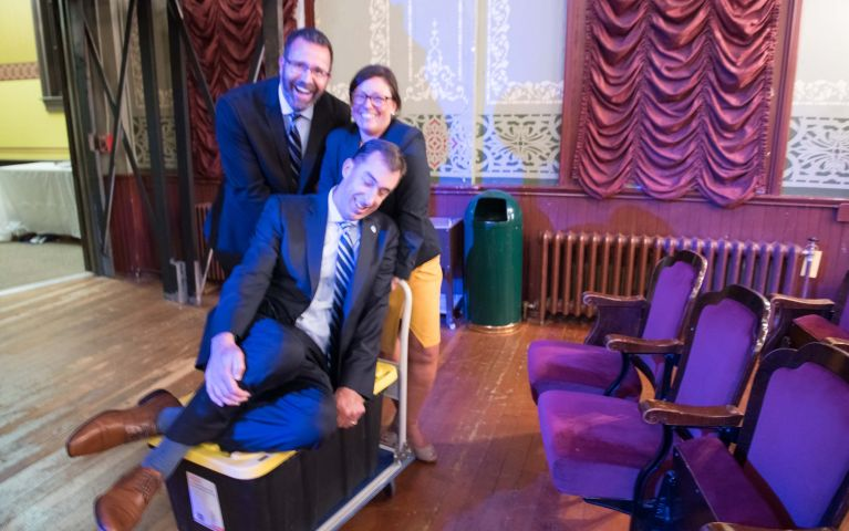 Thomaston Savings Bank employees playfully push CEO and President Stephen L. Lewis on a cart through the theater during the 2019 Foundation Night.