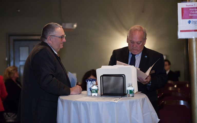 Two men standing together at a table while one looks at a folder at the 2017 Foundation Night