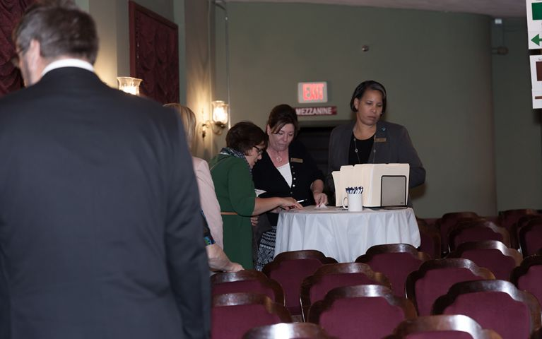 Three women standing around a table with filing folders at the 2017 TSB Foundation Night