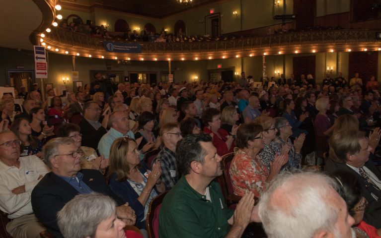 Seated guests fill the theater and clap during TSBs event, a Thomaston Savings Bank flag hangs from the mezzanine.