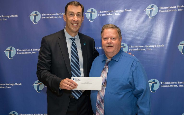 Stephen L. Lewis, CEO and President of Thomaston Savings Bank smiles next to TSB customer while presenting him a check.