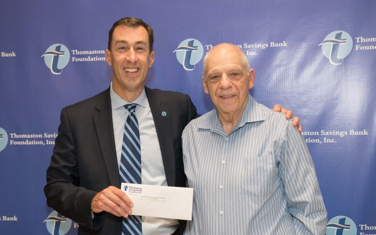 A loyal Thomaston Savings Bank member stands next with the president and CEO of Thomaston Savings Bank for a photo while being presented with an envelope against a blue TSB backdrop at the 2019 Foundation Night.