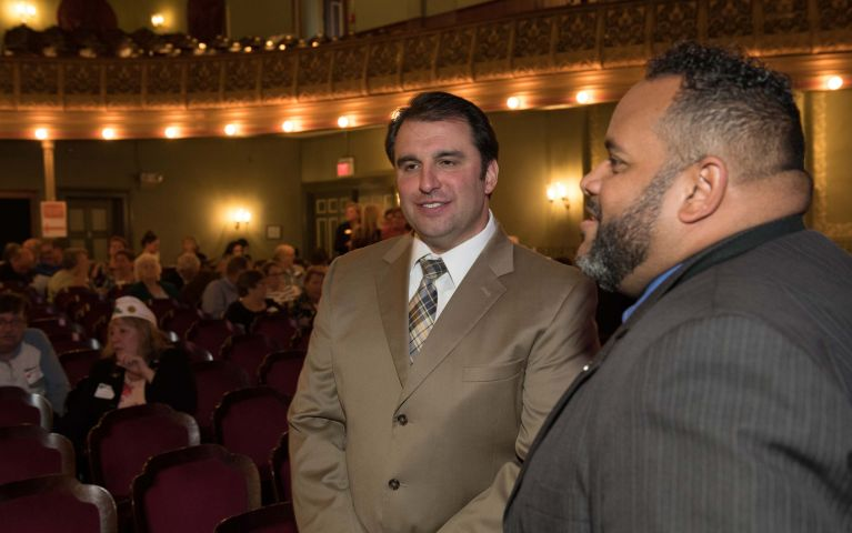 Two gentlemen attendees converse in theater before Thomaston Savings Bank 2019 Foundation Night event.