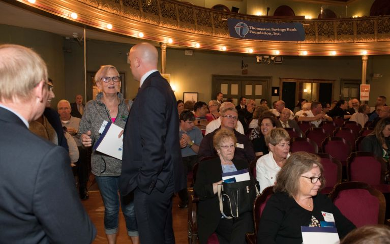 Attendees stand to mingle with others in theater where 2019 Foundation Night is held.