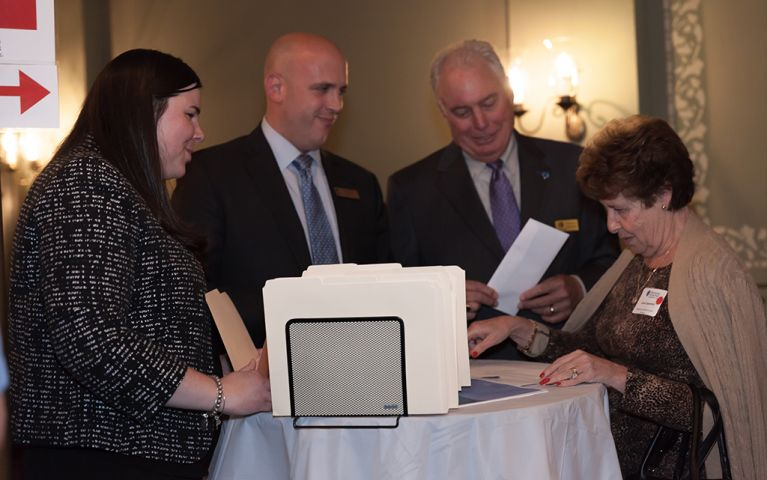 Two men and two women standing around a table, looking at papers at the 2017 TSB Foundation Night