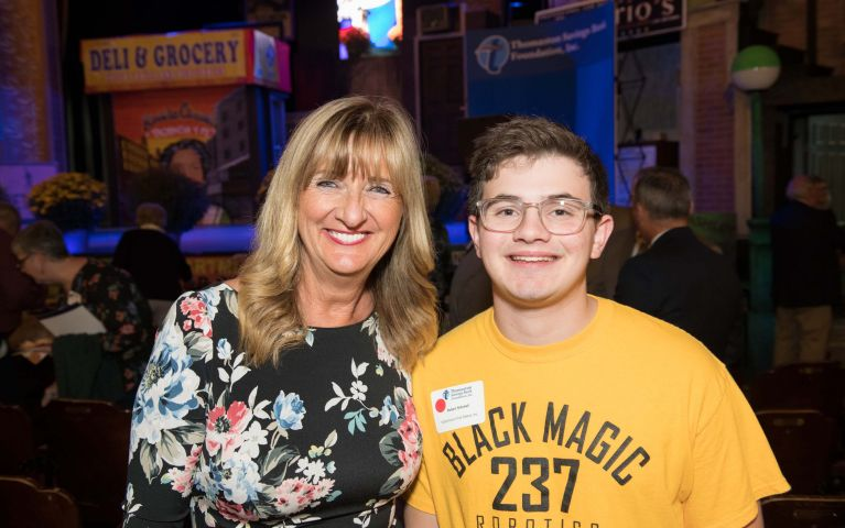 Female attendee poses with young male 237 Black Magic Robotic Team member during 2019 Foundation Night.