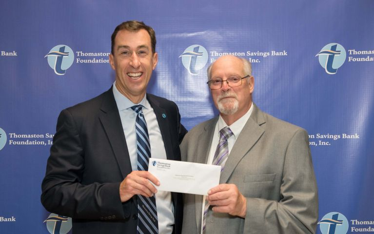Stephen L. Lewis, CEO and president poses with a TSB member and presents him with an envelope against a blue TSB backdrop at the 2019 Thomaston Savings Bank Foundation Night