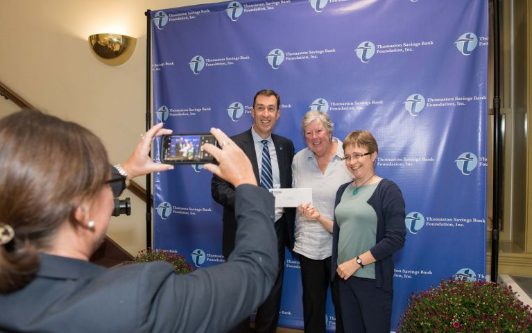 A photo is captured of a TSB member pointing her phone camera at two community members and Stephen L. Lewis, president and CEO while they hold a check at the 2019 Thomaston Savings Bank Foundation Night.