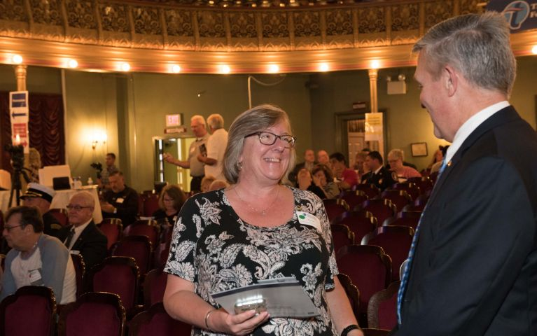 Female attendee greets male attendee in theater during Thomaston Savings Bank 2019 Foundation Night.