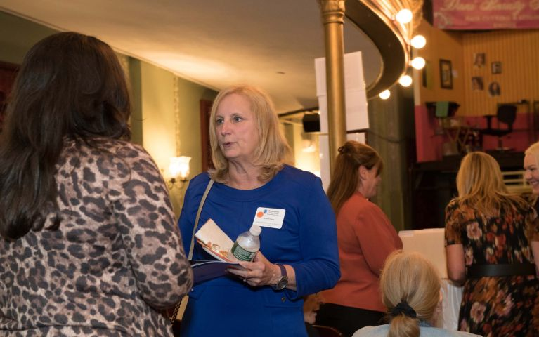 Thomaston Savings Bank 2019 Foundation Night female attendee converses with another female attendee in theater.