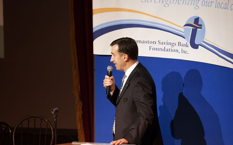 Side profile of President of Thomaston Savings Bank, Stephen L. Lewis, onstage with a microphone at the 2017 Foundation Night
