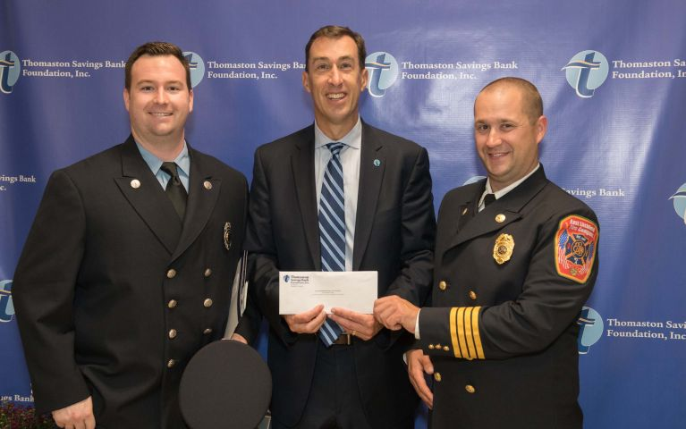 CEO and President of Thomaston Savings Bank, Stephen L. Lewis, with two officers while presenting them an envelope at the 2019 Foundation Night.