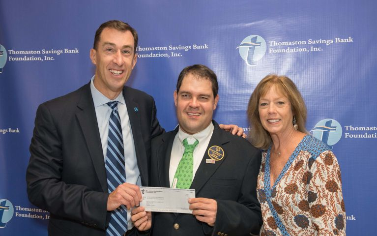 Stephen L. Lewis, President and CEO of Thomaston Savings Bank poses and smiles while presenting a check to local community members for their dedication at the 2019 TSB Foundation Night.