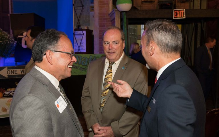 Three male Thomaston Savings Bank members converse during 2019 Foundation Night event.