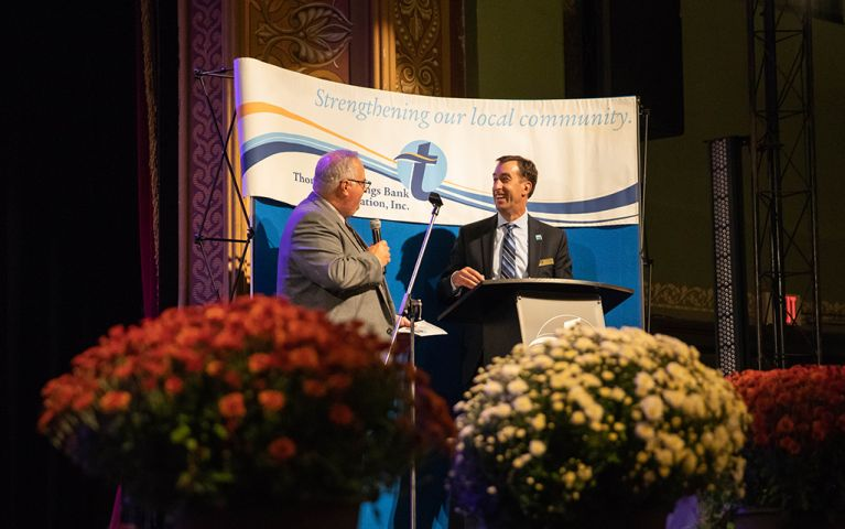 President of Thomaston Savings Bank, Stephen L. Lewis, and another man talking on stage at the 2018 Foundation Night