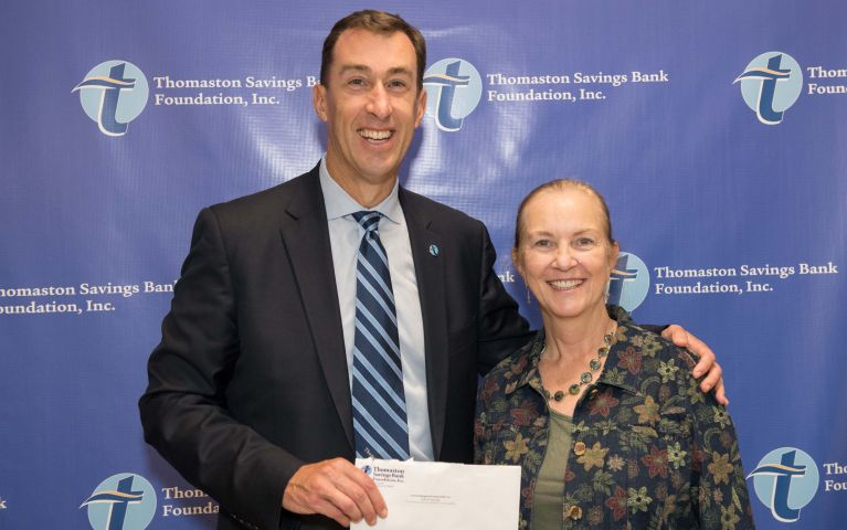 A community member is presented with a check by the President and CEO of Thomaston Savings Bank, Stephen L. Lewis, as they pose for a photo during the 2019 Thomaston Savings Bank Foundation Night.