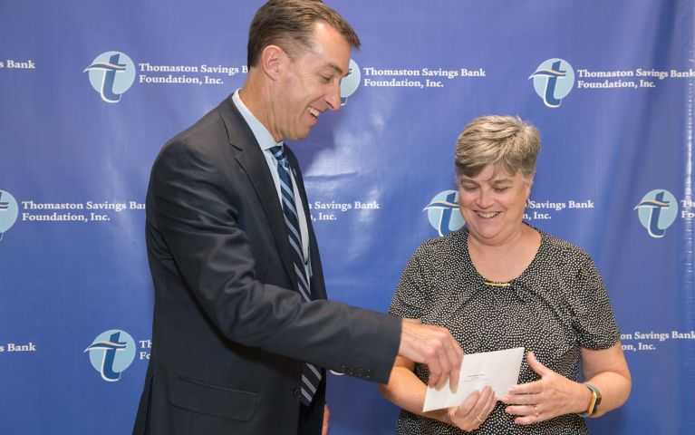 Local female Thomaston Savings Bank member graciously accepts a check from TSB CEO, at 2019 Foundation Night.