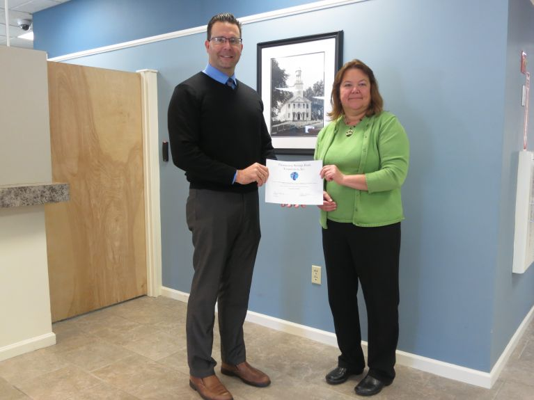 Todd Burton, Assistant Vice President of Retail Banking, presents Harwinton fuel bank donation check to Becky Adkins.