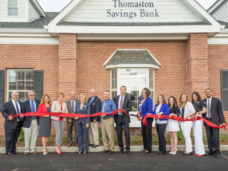 Thomaston Savings Bank members cut a red ribbon, opening the new Bristol branch.